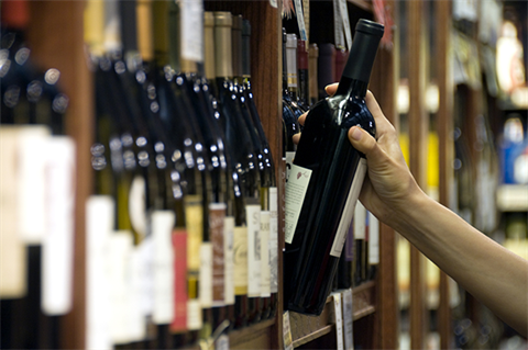 Alcohol Licensing - Fees & Charges - Hand reaching for a wine bottle off the shelf.