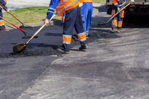 Working on the Road - Roadworkers asphalting and repairing the road.d