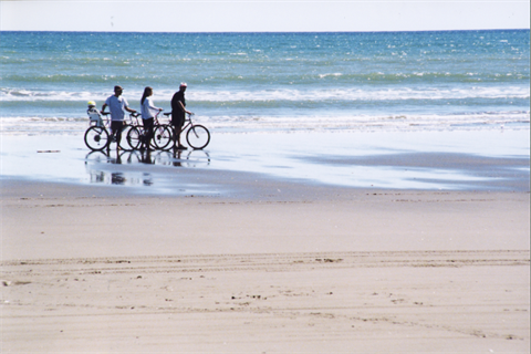 River Mouth Trail - Family walking bikes along the beach's water edge.